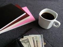 plånbok av kvinnan med amerikanska dollarräkningar, kaffekoppen och staplade böcker royaltyfria bilder