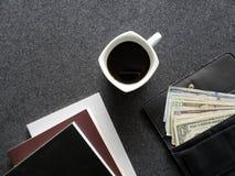 plånbok av kvinnan med amerikanska dollarräkningar, kaffekoppen och staplade böcker arkivfoton