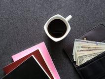 plånbok av kvinnan med amerikanska dollarräkningar, kaffekoppen och staplade böcker royaltyfri bild
