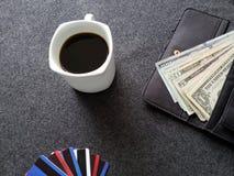 plånbok av kvinnan med den amerikanska dollarräkningar, kaffekoppen och kreditkortar arkivbild
