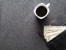 plånbok av kvinnan med dollarsedlar och kaffekoppen på den gråa tabellen fotografering för bildbyråer