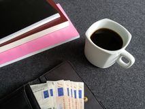 plånbok av kvinnan med eurosedlar, kaffekoppen och staplade böcker royaltyfria foton