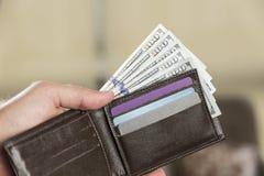 Plånbok med 100 dollarräkningar i en hand för man` s Royaltyfria Foton