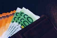 Plånbok med eurosedlar Kassa in plånboken på en svart bakgrund Europengar piskar in plånboken royaltyfri foto