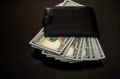 Plånbok med hundra dollarräkningar på en svart reflekterande bakgrund arkivbild