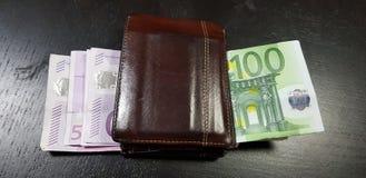 Plånboken som är full med eurosedlar, lägger på den svarta tabellen royaltyfri foto