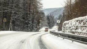Pl?jer den dolda skogv?gen f?r sn?, is p? asfalt, den orange gritteren lastbilen som kommer i avst?ndet, farliga k?rningsvillkor royaltyfria foton