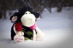Plüschschafe, die eine Rose anhalten und im Schnee sitzen Lizenzfreie Stockfotografie