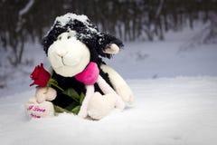 Plüschschafe, die eine Rose anhalten und im Schnee sitzen Stockfoto