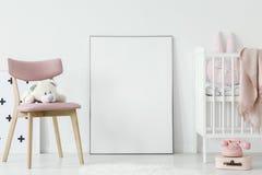 Plüschspielzeug auf rosa Stuhl nahe bei Plakat mit Modell in Baby ` s roo lizenzfreies stockfoto