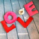 Plüschspielzeug beschriftet L O V E und eine Schale vom Cappuccino mit Herzen Lizenzfreie Stockfotografie