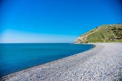 Plaża kamienie wzdłuż błękitnego morza Góry są widoczne w odległości fotografia stock