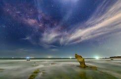 Plaża przy nocą z skałą w kierunku iskrzastego galaxy i gwiazd Zdjęcie Royalty Free
