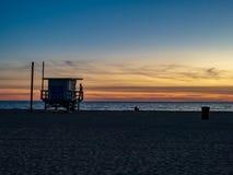 Plaża przy półmroku zmierzchem z ratowników beachgoers i domu relaksować zdjęcie stock