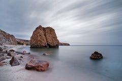 Plaża z czerwonawymi kamieni blokami, wodą i chmura ruchem, obrazy royalty free