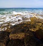 plażowa lekka wa teru piany skały Spain nieba chmury plaża Obraz Royalty Free