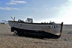 Plażowa scena, A mała drewniana łódź rybacka przechylająca strona opuszczał na otoczakach plaża przy Dungeness zdjęcie royalty free