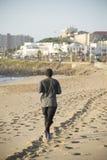 plażowa sprawność fizyczna słuchającego męskiego mężczyzna modela mp3 muzycznego telefonu gracza czerwonego biegacza działającego Zdjęcie Royalty Free