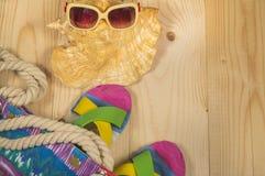 Plażowa torba, trzepnięcie klapy, okulary przeciwsłoneczni, na drewnianym tle Odgórny widok Zdjęcia Royalty Free