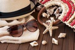 Plażowa torba z ręcznikiem, okularami przeciwsłonecznymi i kapeluszem na drewnianym tle, zdjęcie stock