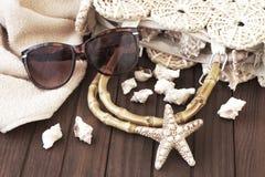 Plażowa torba z ręcznikiem, okularami przeciwsłonecznymi i kapeluszem na drewnianym tle, obraz stock