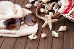Plażowa torba z ręcznikiem, okulary przeciwsłoneczni na drewnianym tle obraz stock