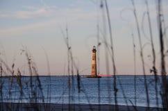 Plażowe trawy i płochy tworzą naturalną ramę z Morris wyspy latarnią morską w SC fotografia stock