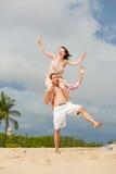 plażowej pary szczęśliwy odprowadzenie utrzymać równowagi Zdjęcia Royalty Free