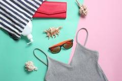 Plażowi akcesoria na barwionym pastelowym tle Plażowa torba, koszulka, okulary przeciwsłoneczni, kiesa, sunblock, cockleshells Od obrazy royalty free