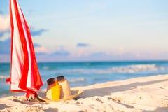 Plażowi akcesoria na piasku dla wakacje pojęcia Parasol, słomiany kapelusz z okularami przeciwsłonecznymi i sunscreen płukanki bu fotografia stock