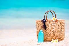 Plażowi akcesoria słomiana torba, hełmofony, butelka śmietanka i okulary przeciwsłoneczni na plaży -, Zdjęcia Royalty Free