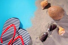 Plażowi akcesoria Trzepnięcie klapy, szkła od słońca, skorupy i koks na piasku morze, W łyżce suchy śniadanie zdjęcia royalty free