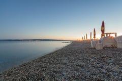 Plażowi klingerytów krzesła i zamknięci parasole na plaży przy zmierzchem obrazy stock
