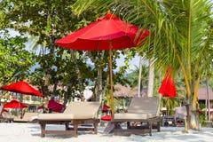 Plażowi krzesła, czerwony parasol i drzewko palmowe na piasku, wyrzucać na brzeg w Tajlandia Obrazy Royalty Free