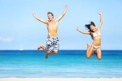 Plażowi ludzie - szczęśliwy pary doskakiwanie obrazy stock