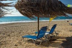 Plażowi słońc łóżka i słomiany parasol na Milos wyrzucać na brzeg na Lefkada wyspie, Grecja - Zdjęcia Stock