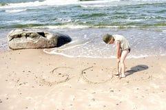 plażowy chłopiec dzieciaka dennego brzeg sos wodny writing Obrazy Royalty Free