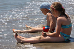 plażowy chłopiec dziewczyny miejsca siedzące Fotografia Stock