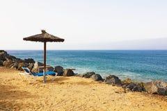 Plażowy parasol i pokładu krzesło na tropikalnej plaży Lanzarote obrazy stock