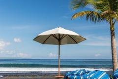 Plażowy parasol na słonecznym dniu, morze w tle Tropikalna plaża z czarnym piaskiem Piękny niebo Raj wyspa Bali Fotografia Stock