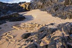 Plażowy piasek Otaczający czerni skały tłem Zdjęcie Royalty Free