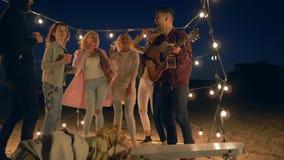 Plażowy przyjęcie, szczęśliwi faceci i dziewczyny z, gitara muzycznym tanem śmiechem w oświetleniu girlandy i zbiory