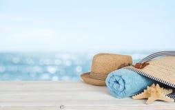 Plażowy ręcznik, torba i kapelusz na drewnie nad defocused oceanem, zdjęcie royalty free