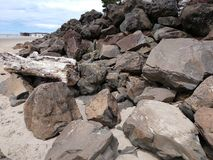 Plażowy stos głazy i driftwood z Plażowym piaskiem w przedpolu przy Oregon wybrzeżem W dalekim tle jest molem zdjęcia stock
