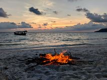 Plażowy zmierzch z ogniskiem i łodzią zdjęcia stock