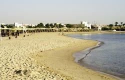Plaża i drzewka palmowe, parasole, domy, niebo Obrazy Royalty Free