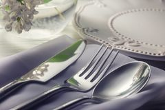 Plaat en bestekvork, lepel, mes op witte houten lijst met witte bloem in vaas Stock Foto's