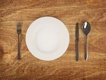 Plaat en tafelgereedschap op houten lijst Stock Foto's