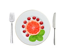 Plaat met Amerikaanse veenbes, grapefruit en muntkruid, lepel en vork i Stock Foto's