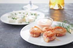 Plaat met bacon verpakte kammosselen en saus Royalty-vrije Stock Foto's
